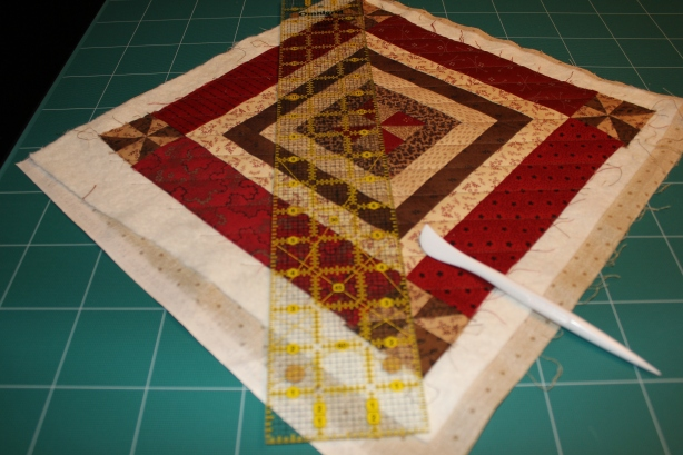 Using a ruler and the Hera...you will run the Hera along the ruler creating a crease, where you will eventually quilt.